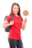 Teenage schoolgirl holding lollipop — Stock Photo