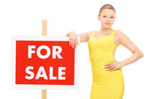 Woman by for sale sign — Stock Photo
