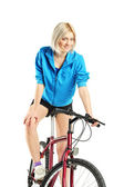 Young female posing on bicycle — Stock Photo
