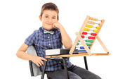 Schoolboy sitting with abacus — Stock Photo