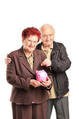 Couple putting money into piggybank — Stock Photo