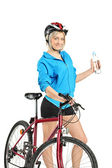 Female cyclist holding water bottle — Stock Photo