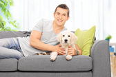 Man on couch with puppy — Stock Photo