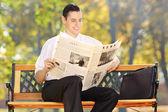 Businessman on bench reading newspaper — Stock Photo