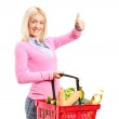 Girl holding a shopping basket full of groceries and giving a th — Stock Photo #49916269