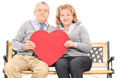Mature couple holding red heart — Stock Photo
