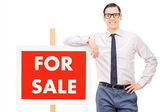 Man leaning on for sale sign — Stock Photo