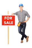 Male repairman leaning on sign — Stock Photo