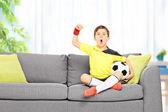 Boy watching football at home — Stock Photo