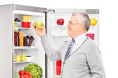 Man taking apple from refrigerator — Stock Photo