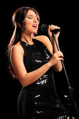 Female musician singing on microphone — Stock Photo