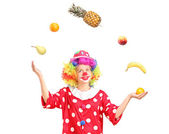 Female clown juggling fruits — Stock Photo