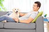 Man with puppy on sofa — Stock Photo