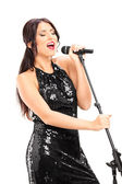 Female singer singing on microphone — Stock Photo