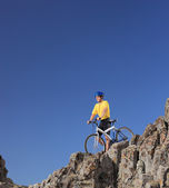 Mountain biker on rocky cliff — Zdjęcie stockowe