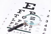 Magnifying glass on eye chart — Photo