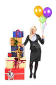 Businesswoman standing by pile of presents — Foto Stock
