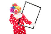 Excited clown holding a big picture frame  — Stock Photo