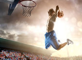 Basketball player in action on background of sky and crowd — Stock Photo