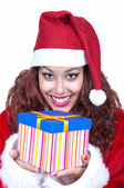 Beautiful brunette wearing santa claus with gift — Stock Photo