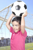Cute boy holding a soccer ball over his head  — Stockfoto