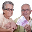 Elderly couple holding bills and piggy bank — Stock Photo #46452443