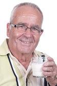 Senior holdsa glass of milk in hand  — Stock Photo