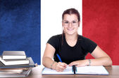 Young girl student pc on the background with french national fla — Stock Photo
