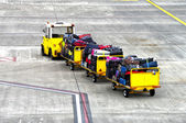 Baggage cars at an airport terminal.  — Stock Photo