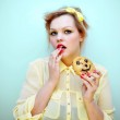 Young attractive woman with red hair and yellow bow headband wearing red lipstick and a yellow chiffon blouse is eating a smiling chocolate chip cookie. — Stock Photo