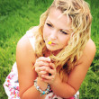 Young woman with blonde curly hair wearing a flower print summer dress is looking away into the distance and smelling a small yellow flower on a green meadow. — Stock Photo #48031275