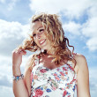 Gorgeous young blonde woman with curly hair wearing a flower print summer dress posing on the background of cloudy blue sky and smiling. — Stock Photo #48031325