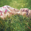Beautiful young woman wearing a flower print summer dress is lying on green grass with her eyes closed. — Stock Photo #48031381
