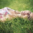 Beautiful smiling young woman wearing a flower print summer dress lying on green grass on the meadow. — Stock Photo #48031443