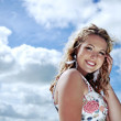 Gorgeous young blonde woman with curly hair wearing a flower print summer dress posing on the background of cloudy blue sky and smiling. — Stock Photo