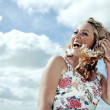 Cheerful young blonde woman with curly hair wearing a flower print summer dress posing and laughing on the background of cloudy blue sky. — Stock Photo