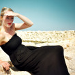 Young blonde attractive woman wearing a long black maxi dress and red lipstick sitting on the rocks by the sea and is holding her hand above her eyes to look far into the distance. — Stok fotoğraf #48038265