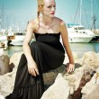 Young blonde woman with plaited hairstyle wearing a long black maxi dress and red lipstick is sitting on the rocks at the marina on the background of luxury boats. — Stock Photo