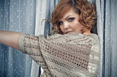 Attractive young woman with short red curly hair and flirtatious blue eyes is standing by the window between long dotted lace curtains with one arm stretched out. — Stock Photo