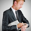 Sophisticated young businessman with light hair wearing a dark grey suit and a tie is holding a newspaper under his arm and looking at the time on his watch. — Stock Photo