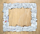 Blank square frame made of shredded pieces of newspaper on a wooden surface. — Stok fotoğraf