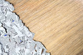 Wooden surface with shredded newspaper pieces gathered in bottom left corner. — Stock Photo