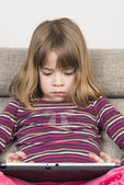 Little girl playing with a digital tablet — Stock Photo