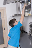 Young boy taking candy from a high kitchen cabinet — Stock Photo