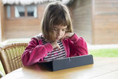Little girl with a digital tablet — Stockfoto