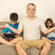 Father and children sitting on the sofa — Stock Photo #49517757