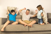 Dad and kids fighting together with pillows — Foto Stock