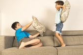 Children fighting together with pillows — Stock Photo
