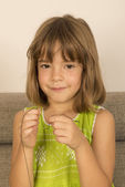Little girl making a necklace — Stockfoto