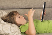 Little girl playing with a digital tablet — Stockfoto